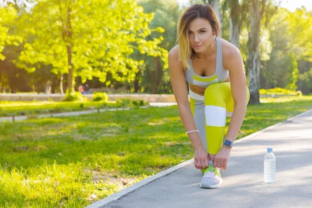 Sportliche frau in laufender anfangshaltung im stadtpark