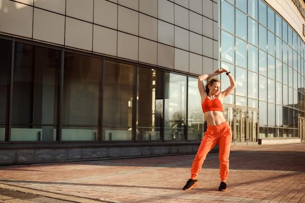 Sportliche frau in orangefarbener sportbekleidung tanzt, wärmt sich draußen vor dem glasgebäude auf, kopierraum.