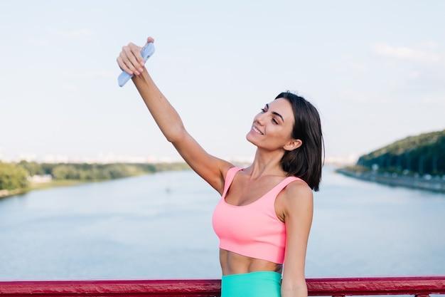 Sportliche frau in passender sportkleidung bei sonnenuntergang an der modernen brücke mit blick auf den fluss glückliches positives lächeln mit handy machen foto-selfie-video für socials-geschichten