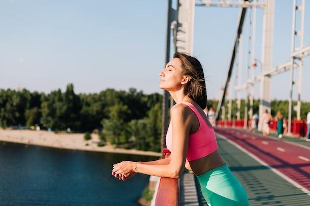 Sportliche frau in passender sportkleidung bei sonnenuntergang an der modernen brücke mit blick auf den fluss, schaut sich um und genießt das sommerwetter