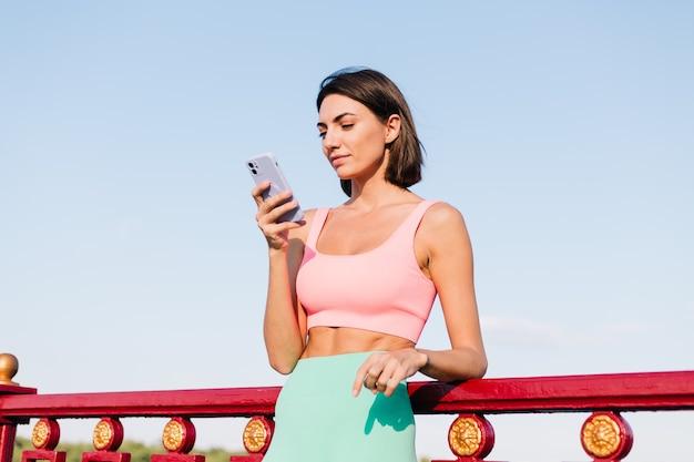 Sportliche frau in passender sportkleidung bei sonnenuntergang an der modernen brücke mit flussblick glückliches positives lächeln mit handyblick auf bildschirm