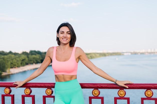 Sportliche frau in passender sportkleidung bei sonnenuntergang an der modernen brücke mit flussblick glückliches positives lächeln