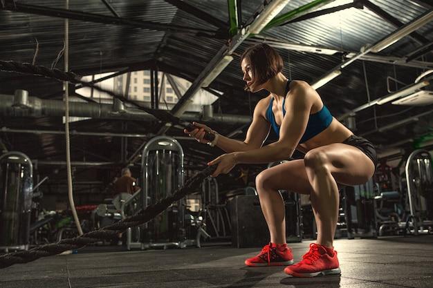 Sportliche frau in sportbekleidung, die kampfseilübung an der funktionellen crossfit-trainingshalle tut