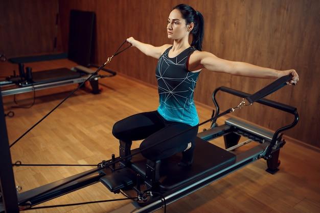 Sportliche frau in sportbekleidung, pilates-training auf trainingsgerät im fitnessstudio.