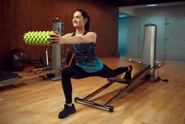 Sportliche frau in sportbekleidung, pilates-training mit roll-on-trainingsgerät im fitnessstudio.