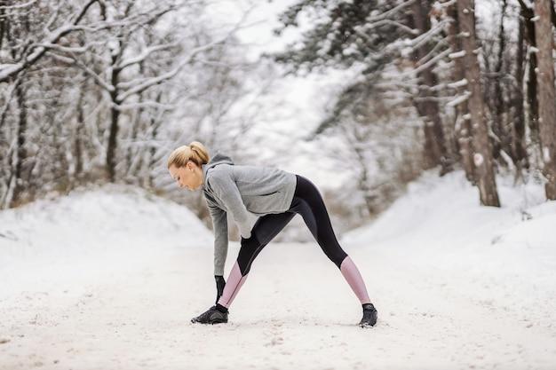 Sportliche frau in warmer sportbekleidung, die aufwärmübungen am verschneiten wintertag in der natur tut.