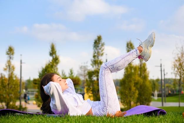 Sportliche frau in weißer kleidung liegt draußen auf der matte und macht stretching, fitness, bauchmuskeln im naturhintergrund