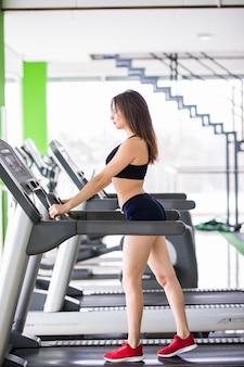 Sportliche frau läuft auf sportsimulator im modernen fitnesscenter in schwarzer sportbekleidung