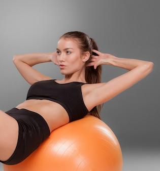 Sportliche frau macht aerobic-übungen auf einem fitnessball auf grauem hintergrund