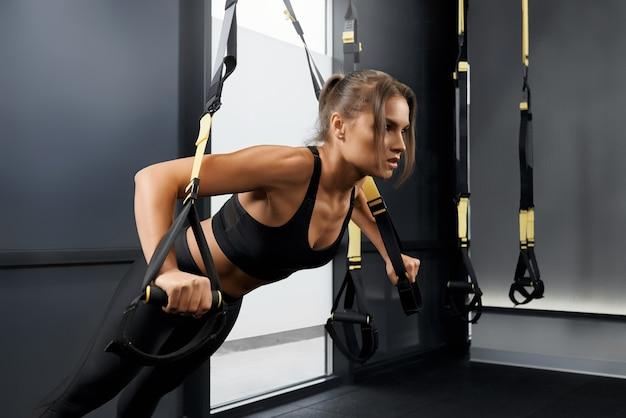 Sportliche frau macht trainingsübung mit trx