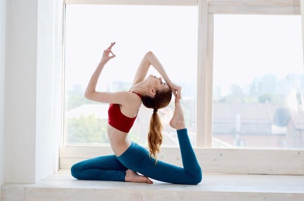 Sportliche frau macht yoga-übungen am fenster