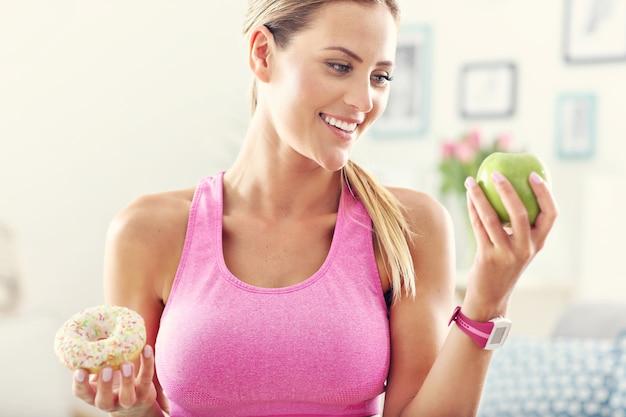 Sportliche frau mit apfel und donut nach dem training Premium Fotos