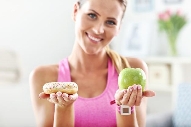 Sportliche frau mit apfel und donut nach dem training