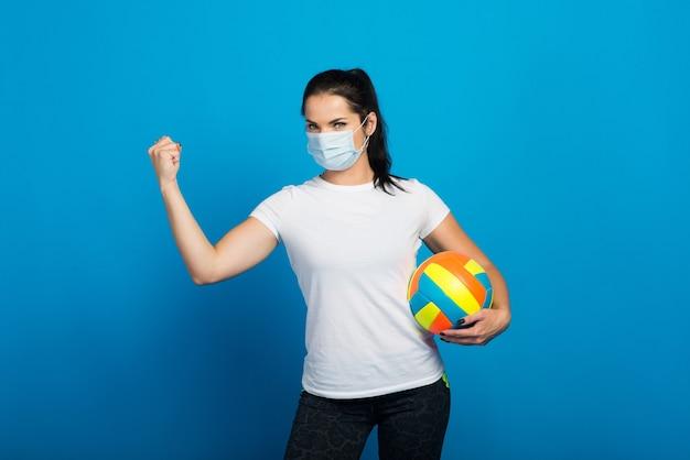 Sportliche frau mit gesichtsmaske vom halten eines volleyballballs