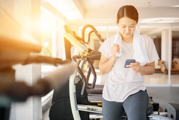 Sportliche frau mit handy beim training. asiatische frau übt allein und lebensstil im fitness-studio aus. wellness und gesund.