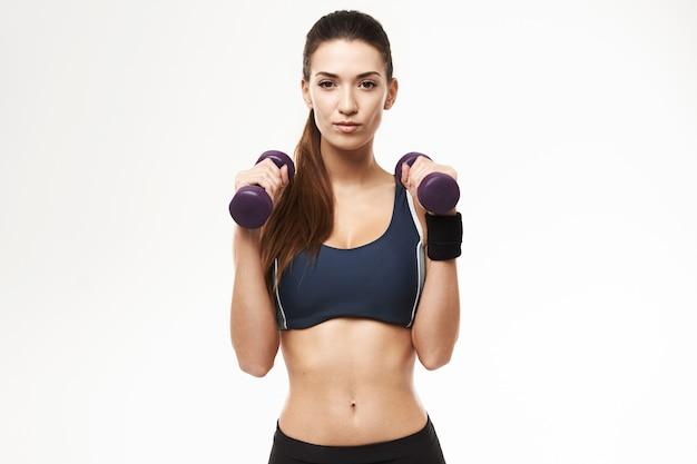 Sportliche frau mit hanteln in der sportkleidung, die auf weiß aufwirft.