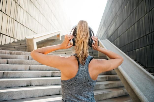 Sportliche frau mit kopfhörern in der städtischen umwelt