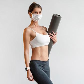 Sportliche frau mit medizinischer maske, die yogamatte hält