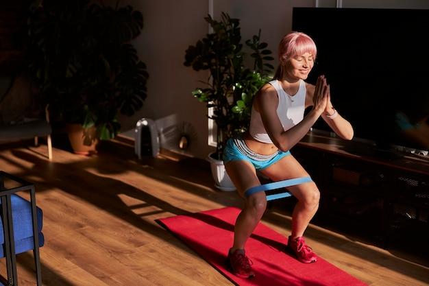 Sportliche frau mit rosa haaren macht zu hause übungen mit gummiband