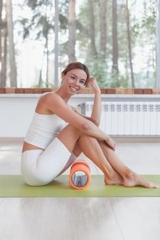 Sportliche frau mit schaumstoffrolle sitzt auf matte in der sporthalle