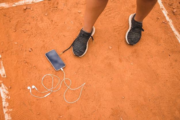Sportliche frau mit smartphone auf stadionsbahn