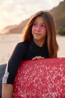 Sportliche frau mit surfzink, gekleidet in schwarzen neoprenanzug, hält gewachstes surfbrett