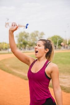 Sportliche frau mit wasserflasche auf stadionsbahn