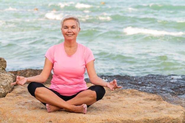 Sportliche frau mittleren alters, die am strand meditiert und lächelt