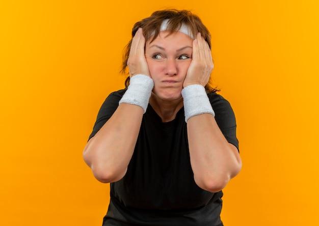 Sportliche frau mittleren alters im schwarzen t-shirt mit dem stirnband, das beiseite geschockt schaut, hielt ihr gesicht mit armen, die über orange wand stehen