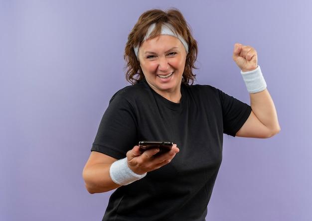 Sportliche frau mittleren alters im schwarzen t-shirt mit dem stirnband, das die geballte faust des smartphones hält, glücklich und aufgeregt lächelnd fröhlich über der blauen wand stehend