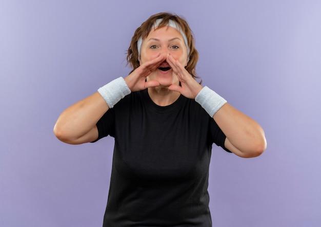 Sportliche frau mittleren alters im schwarzen t-shirt mit dem stirnband, das jemanden mit den händen nahe dem mund schreit oder ruft, der über der blauen wand steht