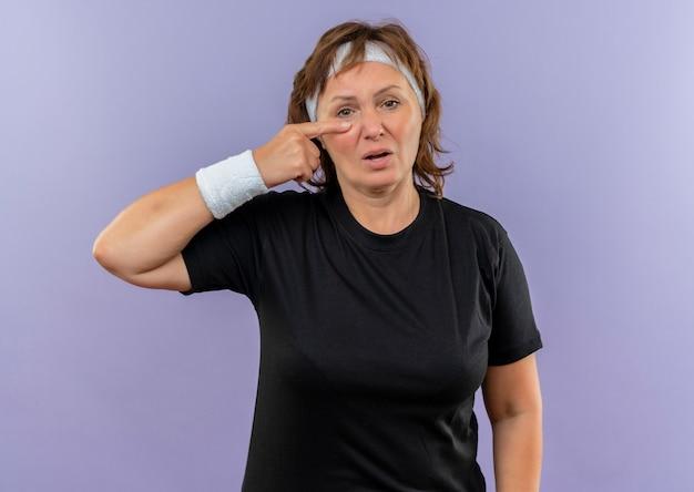 Sportliche frau mittleren alters im schwarzen t-shirt mit dem stirnband, das mit dem finger auf ihre nase zeigt und verwirrt über der blauen wand steht