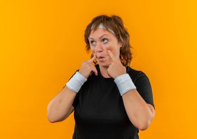 Sportliche frau mittleren alters im schwarzen t-shirt mit dem stirnband, das mit den fingern zu ihren augen zeigt, die sie beobachten, wie sie über orange wand stehen
