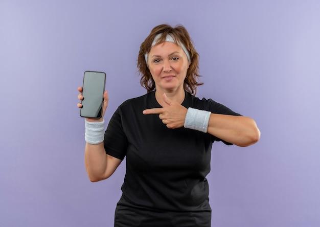 Sportliche frau mittleren alters im schwarzen t-shirt mit dem stirnband, das smartphone zeigt, das mit dem finger auf ihn zeigt, der zuversichtlich über der blauen wand steht