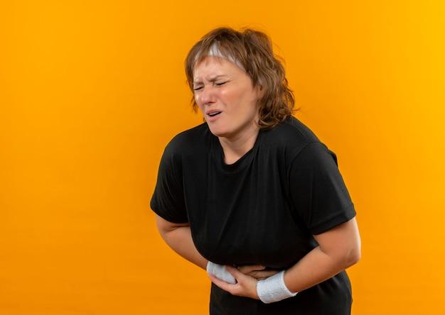 Sportliche frau mittleren alters im schwarzen t-shirt mit dem stirnband, das unwohl schaut, das ihren bauch berührt, der unter schmerzen leidet, die über orange wand stehen