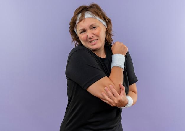 Sportliche frau mittleren alters im schwarzen t-shirt mit dem stirnband, das unwohl schaut, das ihren ellbogen berührt, der schmerz fühlt, der über blauer wand steht