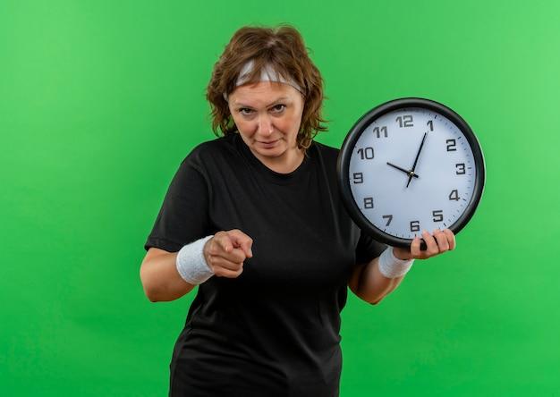 Sportliche frau mittleren alters im schwarzen t-shirt mit dem stirnband, das wanduhr hält, zeigt mit finger zur kamera mit ernstem gesicht, das über grüner wand steht