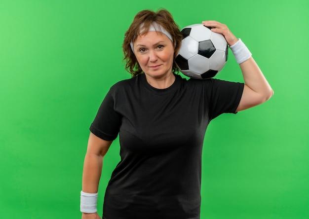 Sportliche frau mittleren alters im schwarzen t-shirt mit dem stirnband, der fußball mit ernstem sicherem ausdruck hält, der über grüner wand steht