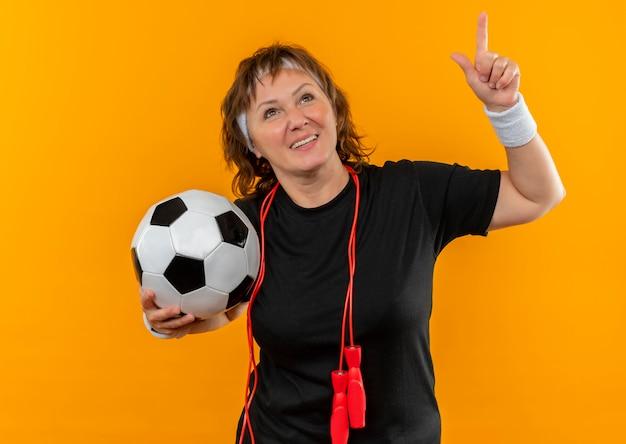 Sportliche frau mittleren alters im schwarzen t-shirt mit dem stirnband, der fußball zeigt, der mit dem zeigefinger oben lächelt und über orange wand steht