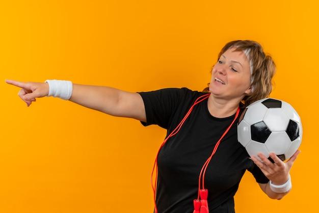 Sportliche frau mittleren alters im schwarzen t-shirt mit dem stirnband, der fußball zeigt, zeigt mit dem finger zur seite lächelnd über orange wand stehend