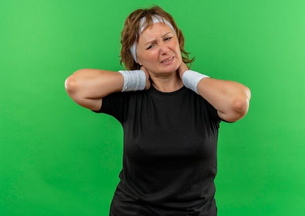 Sportliche frau mittleren alters im schwarzen t-shirt mit dem stirnband, der unwohl schaut, ihren nacken berührend fühlt schmerz, der über grüner wand steht