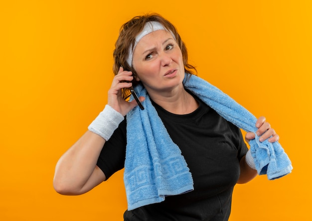 Sportliche frau mittleren alters im schwarzen t-shirt mit dem stirnband und dem handtuch auf der schulter, die müde spricht, die auf handy steht, das über orange wand steht