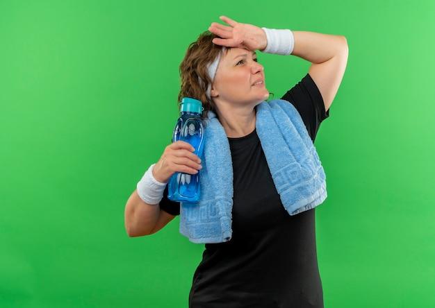 Sportliche frau mittleren alters im schwarzen t-shirt mit stirnband und handtuch an ihrem hals, die flasche wasser halten, das müde und erschöpft über grüner wand steht