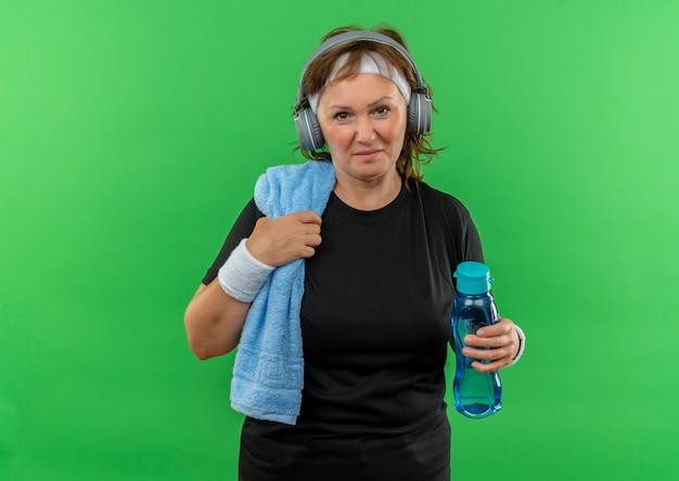 Sportliche frau mittleren alters im schwarzen t-shirt mit stirnband und handtuch an ihrem hals, die flasche wasser müde und glücklich nach dem ausarbeiten stehen über grüner wand hält
