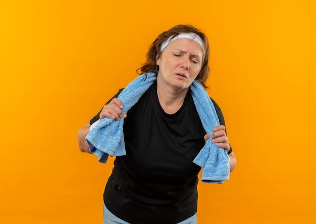 Sportliche frau mittleren alters im schwarzen t-shirt mit stirnband und handtuch auf der schulter, die müde und erschöpft nach dem training über der orangefarbenen wand stehen