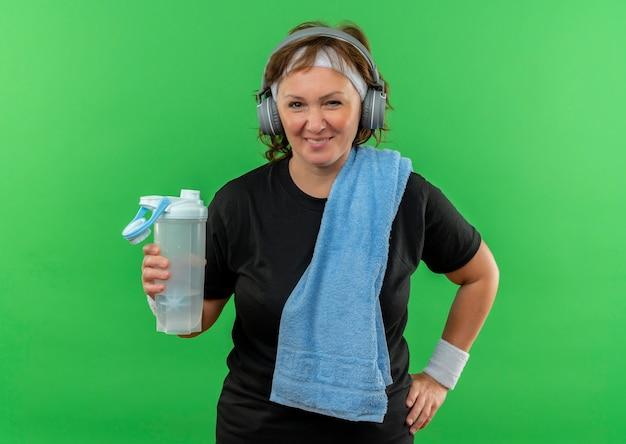 Sportliche frau mittleren alters im schwarzen t-shirt mit stirnband und handtuch auf ihrem hals, der flasche wasser lächelnd glücklich und positiv steht über grüner wand hält