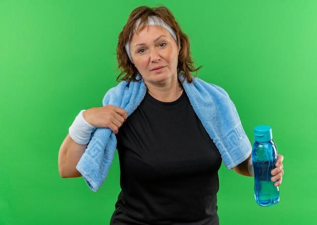 Sportliche frau mittleren alters im schwarzen t-shirt mit stirnband und handtuch auf ihrem hals, der flasche wasser verwirrt hält, das über grüner wand steht