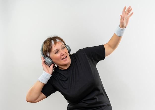 Sportliche frau mittleren alters im schwarzen t-shirt mit stirnband und kopfhörern, die glücklich und positiv ihre lieblingsmusik genießen, die über weißer wand steht