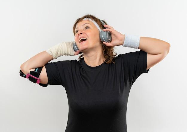 Sportliche frau mittleren alters im schwarzen t-shirt mit stirnband und kopfhörern, die ihre lieblingsmusik glücklich und positiv lächelnd über weißer wand stehend genießen