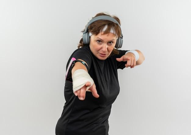 Sportliche frau mittleren alters im schwarzen t-shirt mit stirnband und kopfhörern, die mit zeigefingern zeigen, die über weißer wand stehen